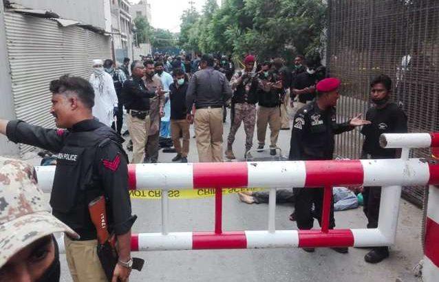 Policiais vigiam um carro usado por supostos homens armados do lado de fora do prédio da Bolsa de Valores do Paquistão em Karachi (Reprodução/Internet)