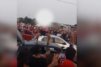 Menina está em cima de um carro, ao redor de várias pessoas que filmam e estão sem máscaras de proteção. (Reprodução/Internet)