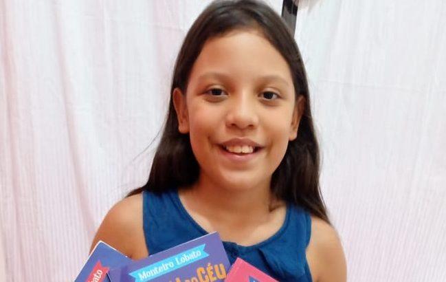 A pequena leitora Lívya Reateque, de Rondônia, mostra os três livros já lidos nas lives iniciadas em maio (Divulgação/ Arquivo de família)