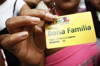 Beneficiária segura o cartão do Bolsa Família (Reprodução/ Internet)