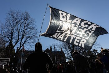 Manifestantes erguem a bandeira do Black Lives Matter durante protesto por justiça para George Floyd, em St. Paul, Minnesota (Foto: Kerem Yucel/AFP)