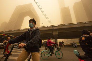 Ciclistas em meio a tempestade de areia durante o horário de rush no distrito comercial de Pequim nesta segunda-feira, 15 (Foto: Mark Schiefelbein/AP)