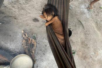 Com quadro de verminose e malária, criança yanomami dorme em rede na aldeia Maimasi, perto da Missão Catrimani, na Terra Indígena Yanomami, em Roraima (Reprodução/Folha de S. Paulo)