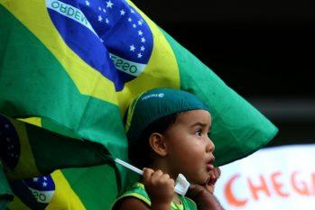 Com olhar expressivo de quem é o futuro do País, uma criança vestida de verde e amarelo carrega bandeira do Brasil em manifestação. (Ricardo Oliveira/ Cenarium)