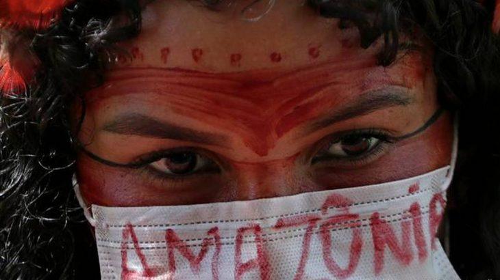 Mulher indígena protesta contra Bolsonaro em Brasília em abril de 2020 (Eraldo Peres/ AP Photo/ picture alliance)